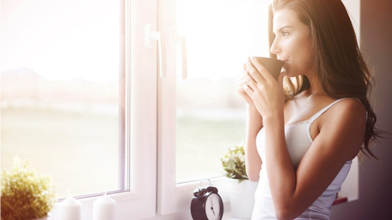 Woman lounging at home and drinking coffee