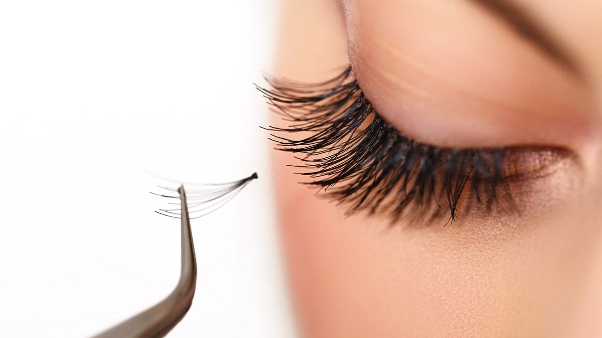 Woman applying fake eyelashes