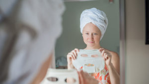 Woman holding sheet masks a must-have summer beauty hack