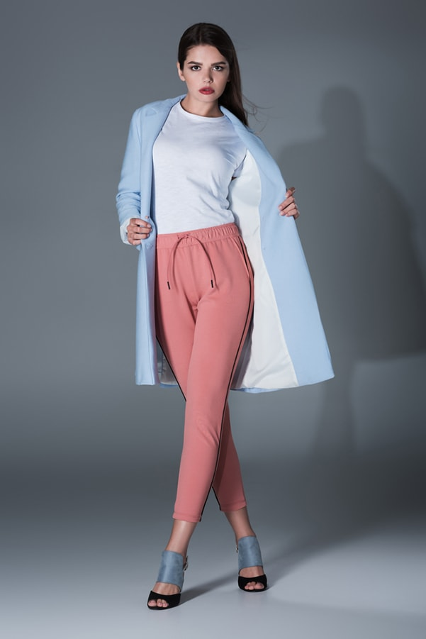 Woman wearing blue trenchcoat and peach sweatpants