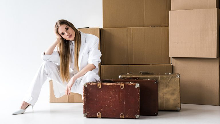 Woman sitting in front of boxes and suitcases