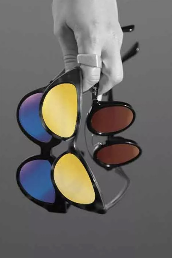 Hand holding sunglasses with different colored lens