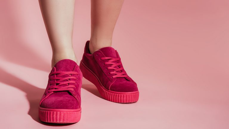 Close up of women's legs with bright pink platform sneakers