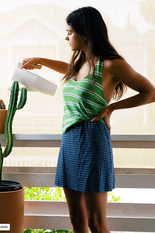 Girl wearing a-line mini skirt and watering a plant.