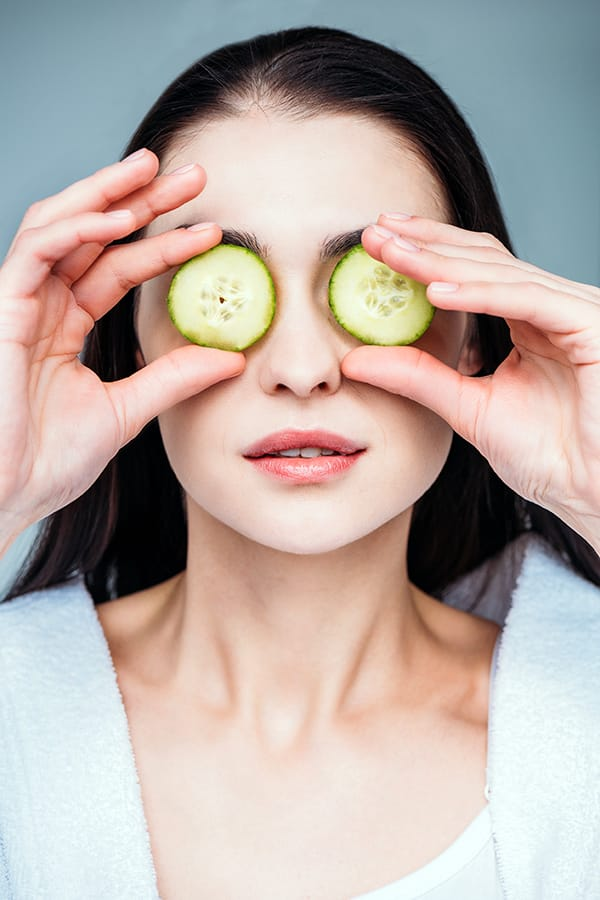 Woman holding cucumbers over her eyes, a skincare home remedy for sagging eyelids.