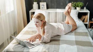 Woman wearing robe at home, on bed with laptop.