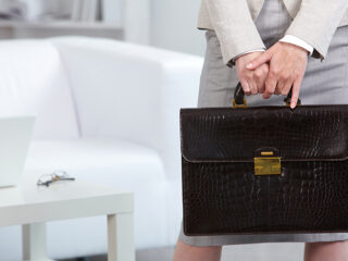 Close-up of woman holding brown leather briefcase with gold details.