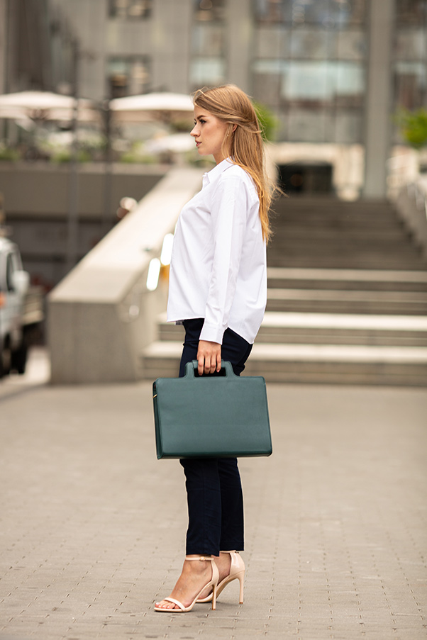 Woman wearing white button down top and black pants, carrying green leather briefcase.