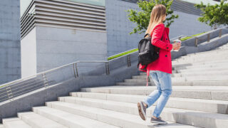 Woman wearing not so skinny jeans walking up stairs.