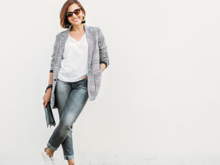 Stylish woman standing in front of grey background.