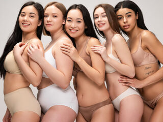 A multiethnic group of five women wearing different types of panties.