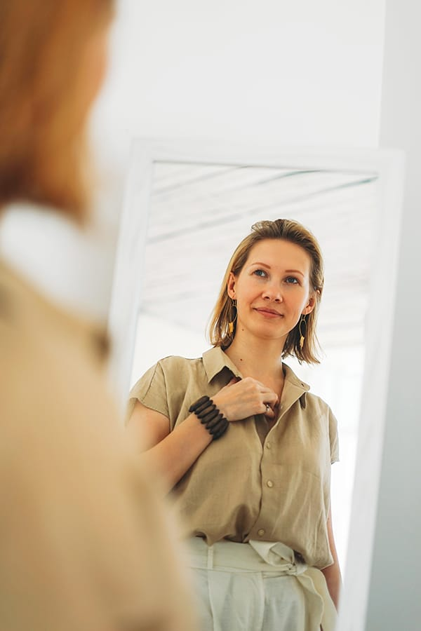 """Woman looking at her outfit in the mirror, thinking, """"I have no style."""""""