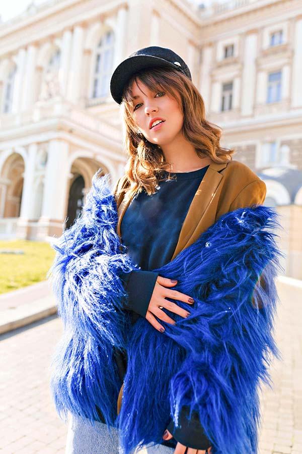 Fashion model wearing blue fur coat and baseball hat.