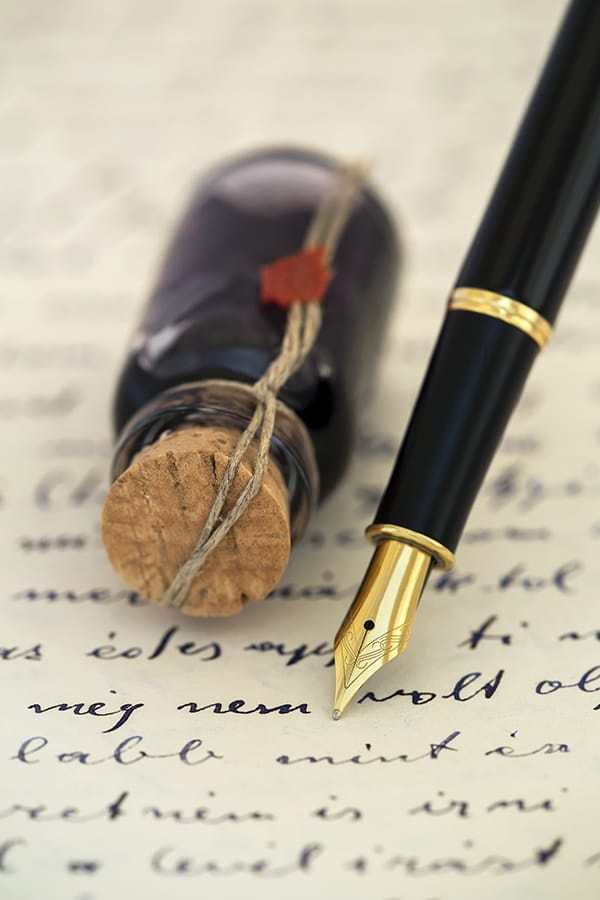 Fountain pen with ink bottle on top of handwritten note.