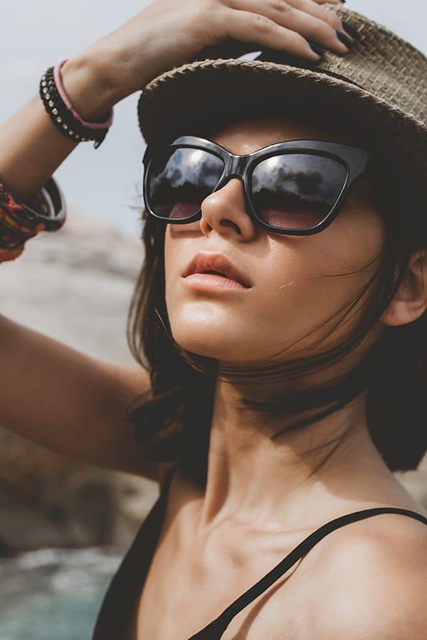 Close up of stylish woman wearing sunglasses and hat.