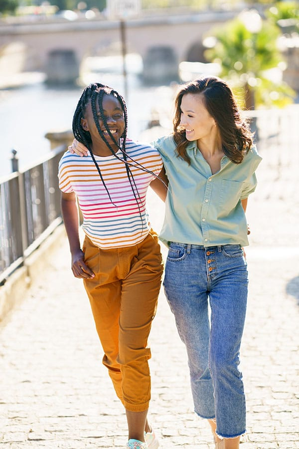 Two young women friends walking down the street together laughing.