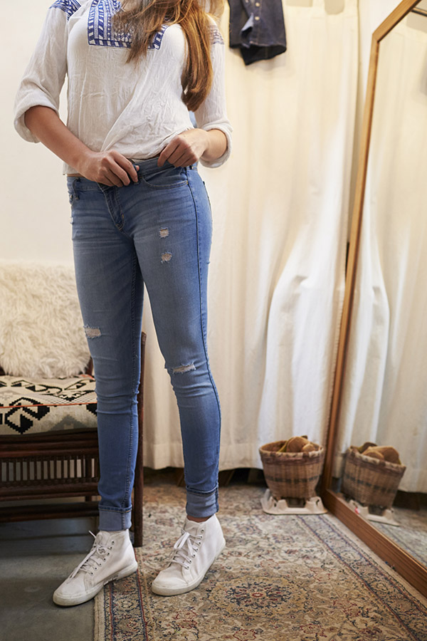 Woman trying on jeans and looking in the mirror.