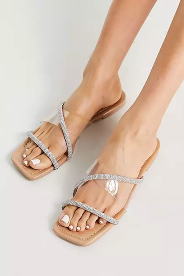 Flat sandal with clear band and embellished straps.
