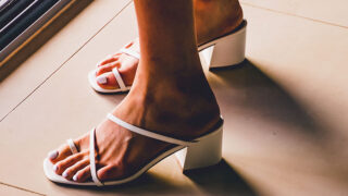 Close up of strappy white heeled sandals on woman's feet.