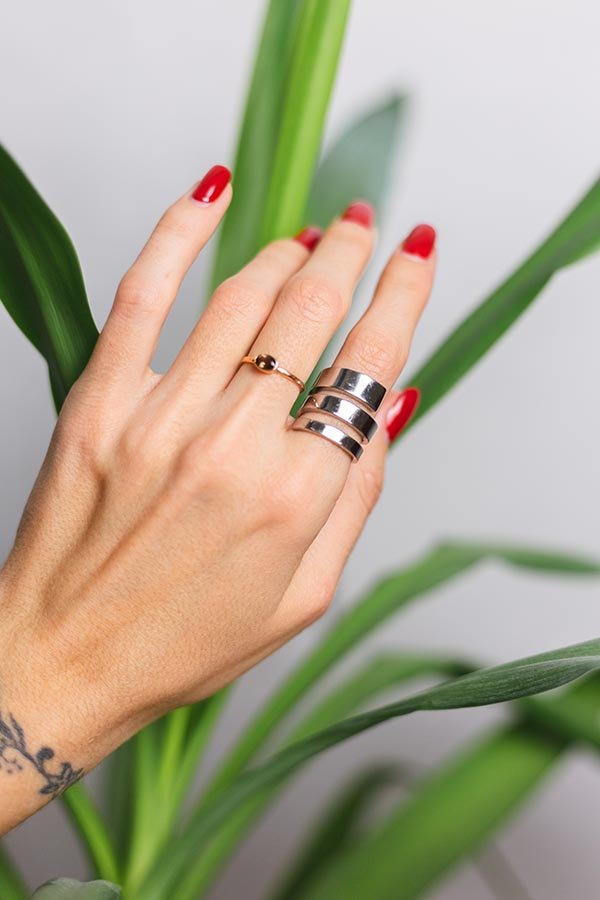Close up of woman's fingers with ring stack.