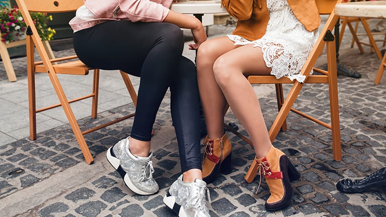 Close up of two women together, one who is wearing an outfit with leggings.