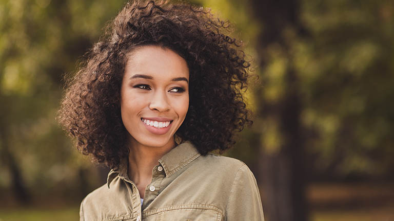 Adult woman with healthy curly hair thanks to natural hair care ingredients.