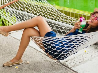 Woman on summer vacation sitting in hammock and sipping cocktail.