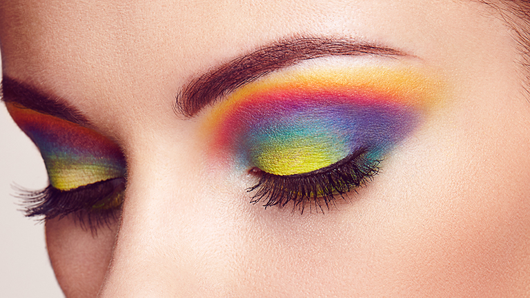 Close up of woman with rainbow eyeshadow, one of our summer makeup trends.