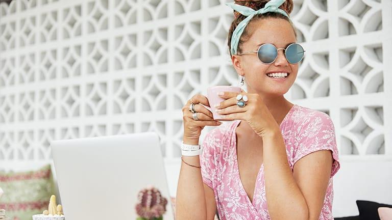 Woman wearing key fashion basics -- sunglasses, jewelry, and scarf.