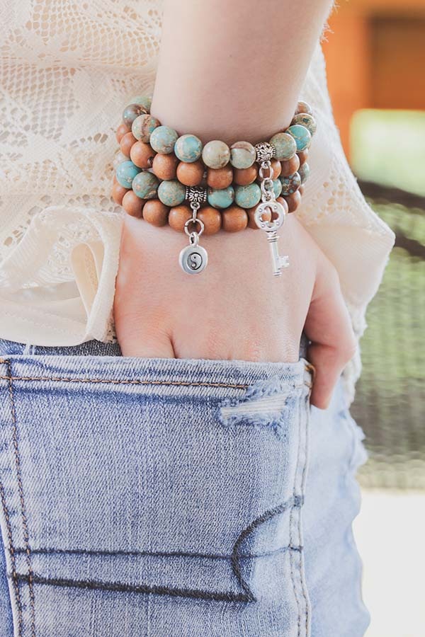 Close-up of woman wearing stack of bracelets.