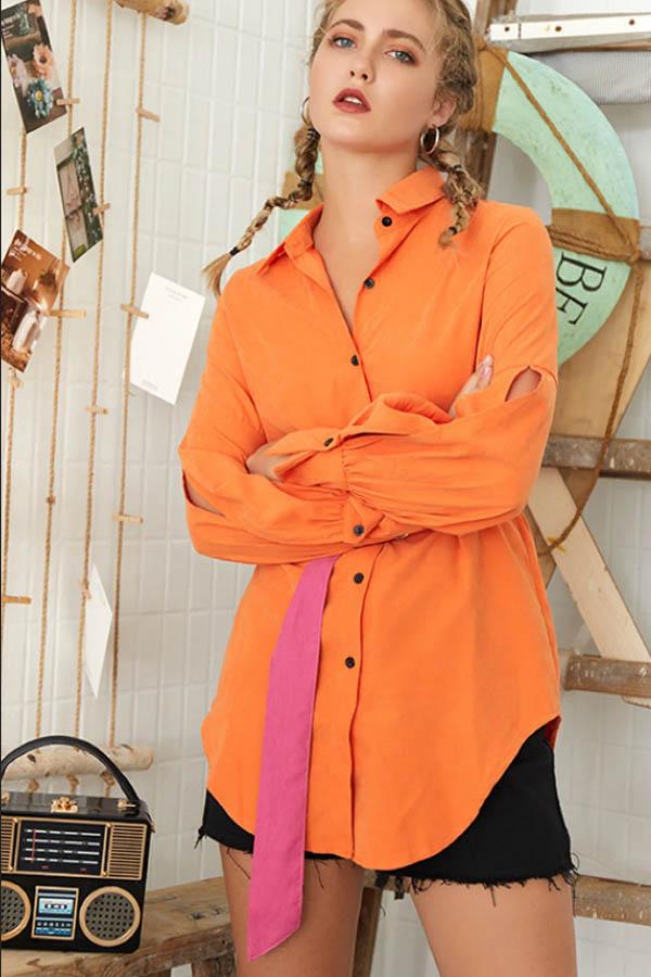 Orange long shirt with pink belt.