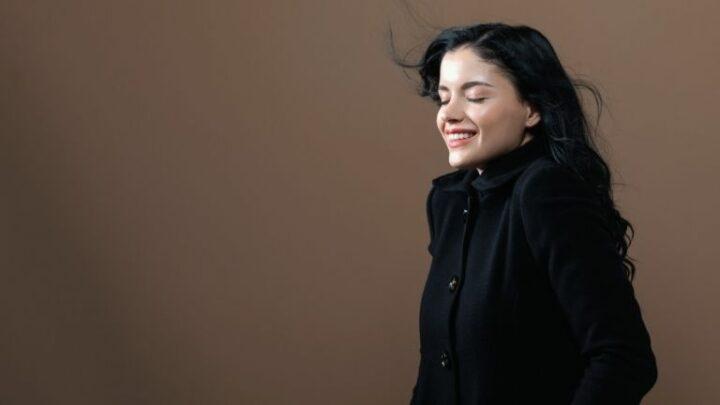 Woman smiling wearing a trendy coat.